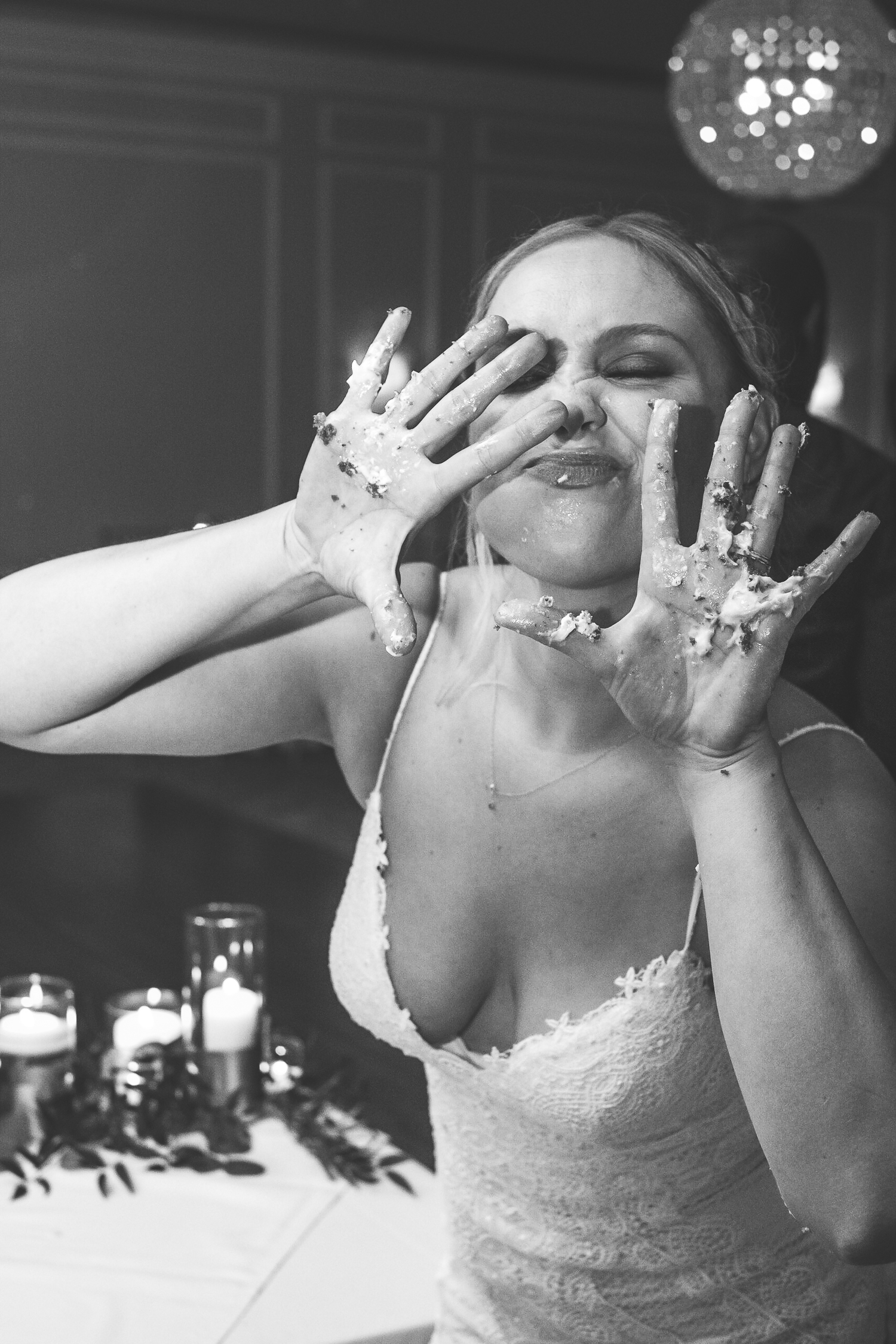bride hands covered in cake making funny face at camera