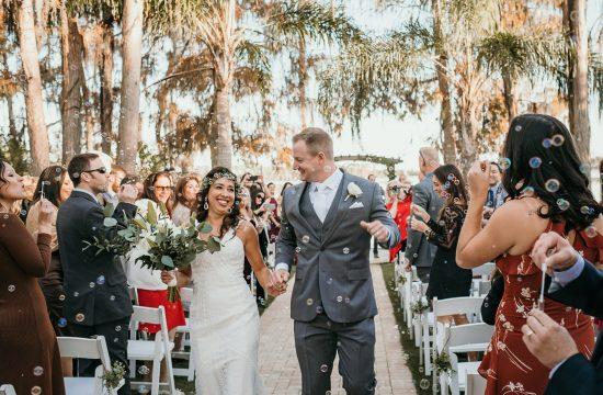 newlyweds walking down isle bubbles