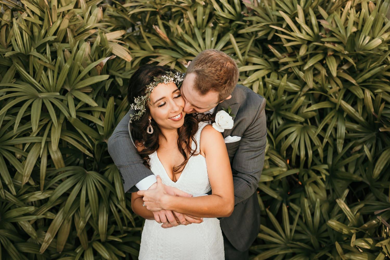 newlyweds hugging palm trees background
