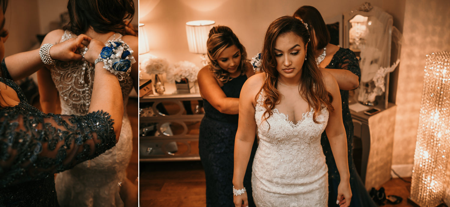 mom and sister help bride with dress
