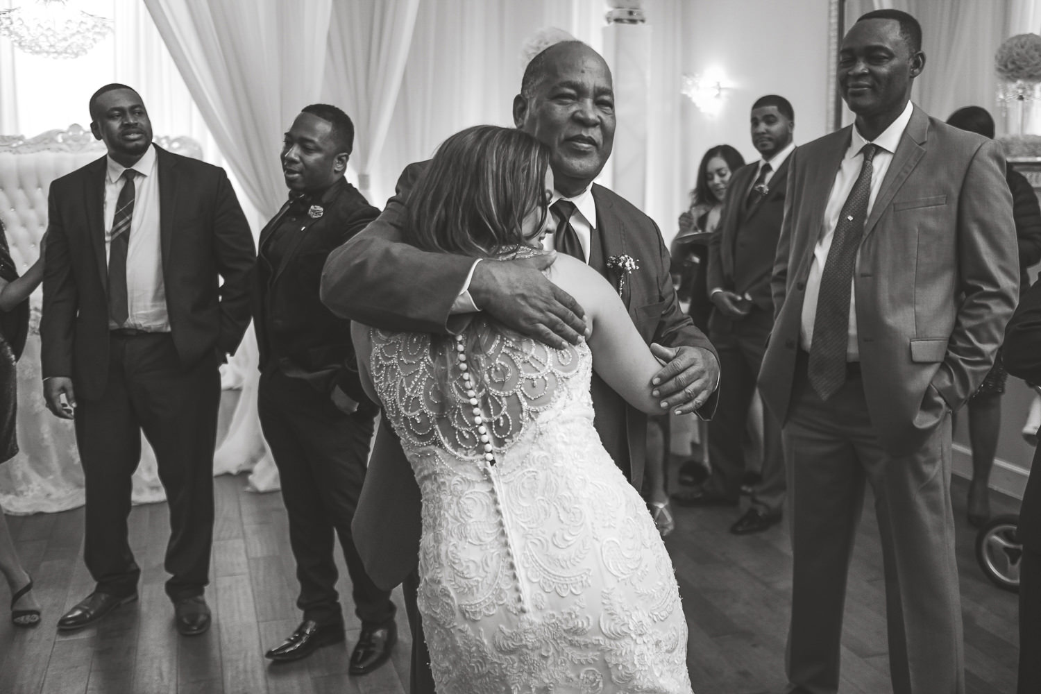 grooms father hugging bride black and white