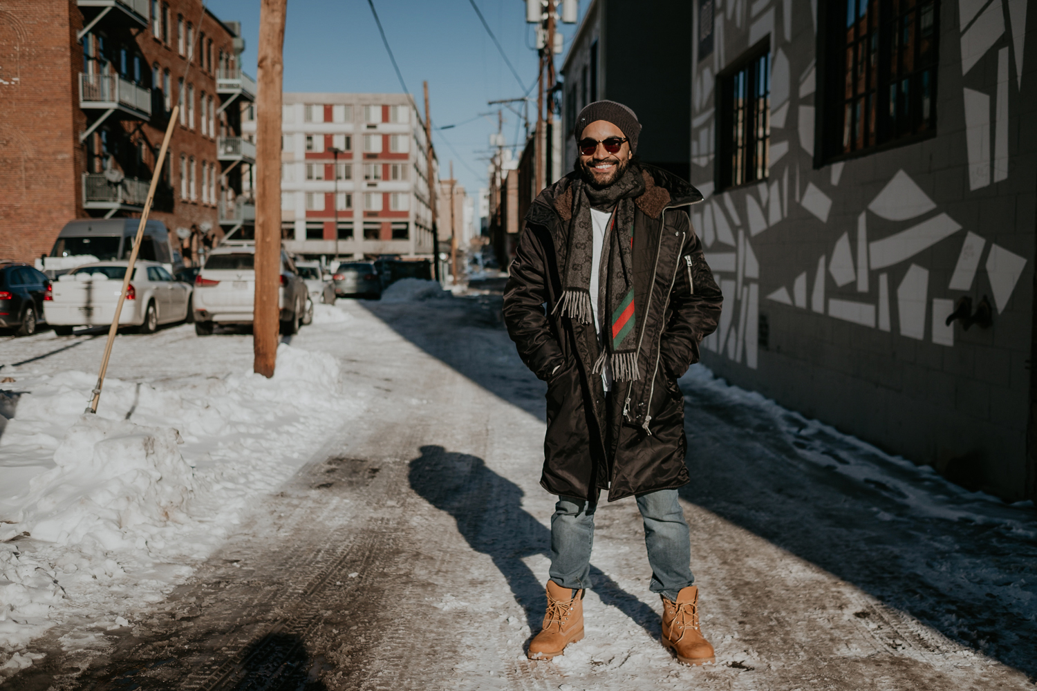 Ector laughing standing on snow wearing timberlands and long black jacket