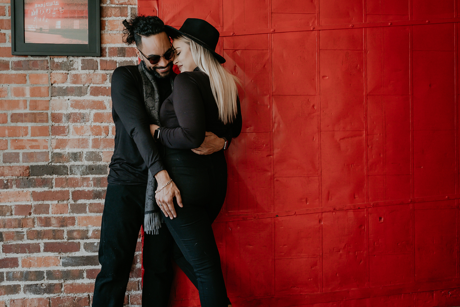Tessa and Ector hugging in front of red wall wearing all black