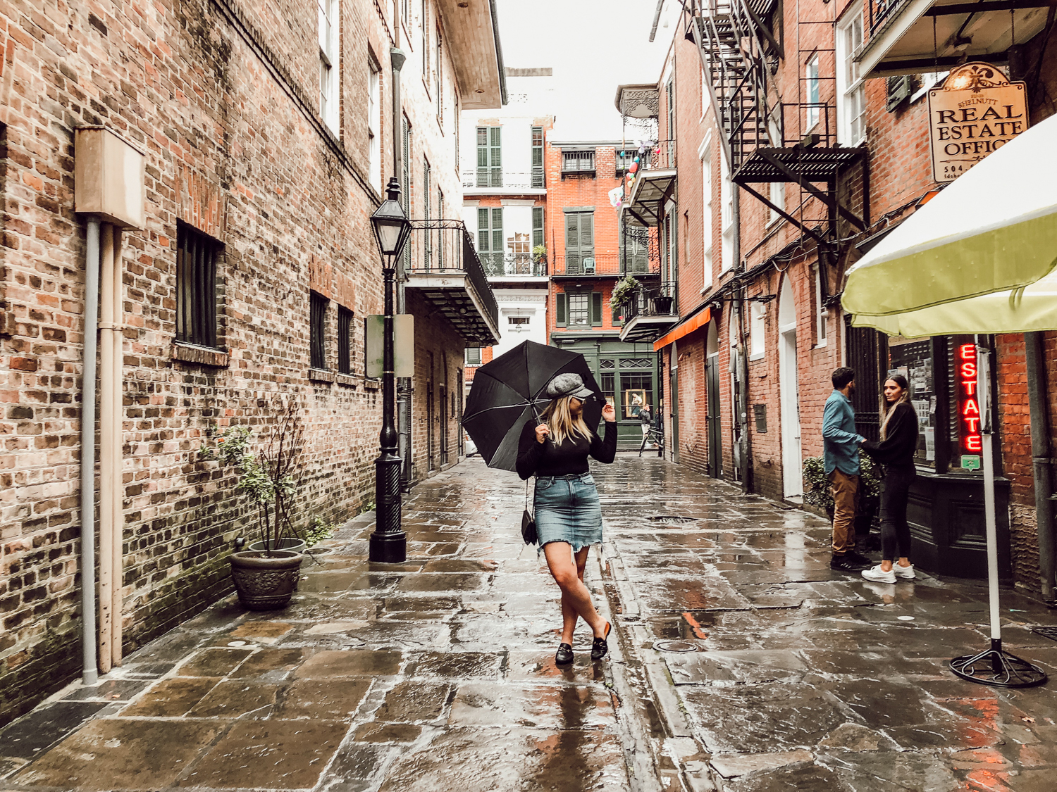 wide shot of Tessa in alley holding umbrella looking to the side