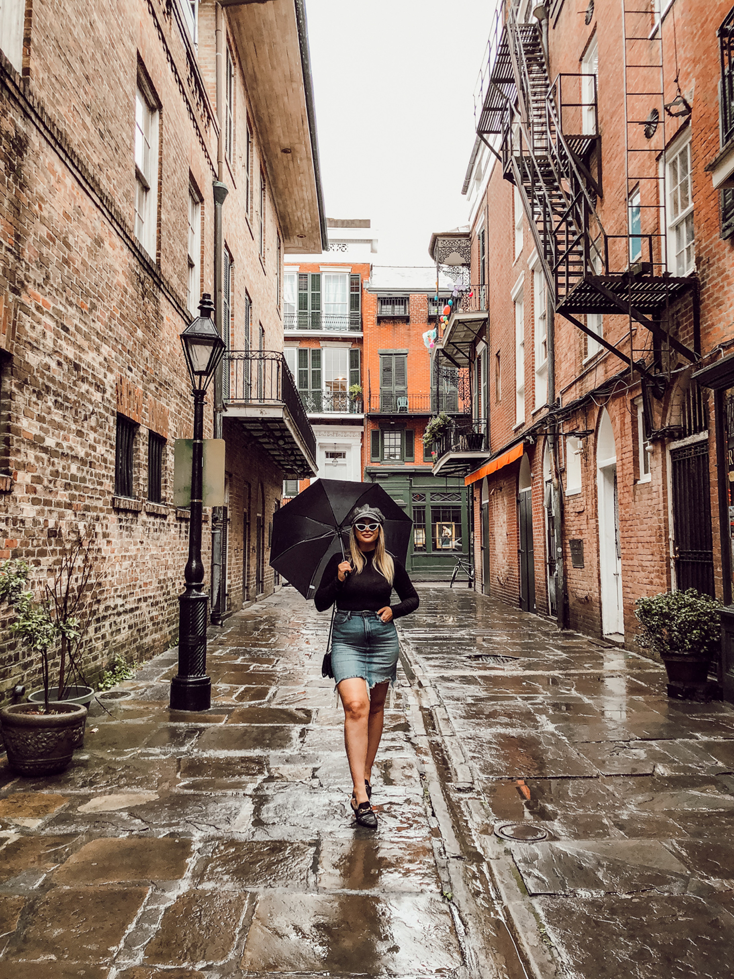 Tessa with sunglasses holding umbrella in Nola alley