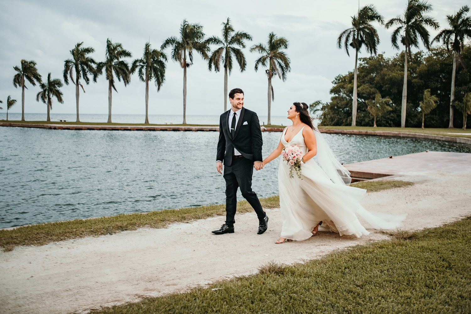 bride and groom walking back palm trees in background
