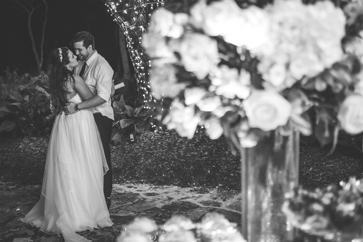 bride and groom secretly kissing black and white