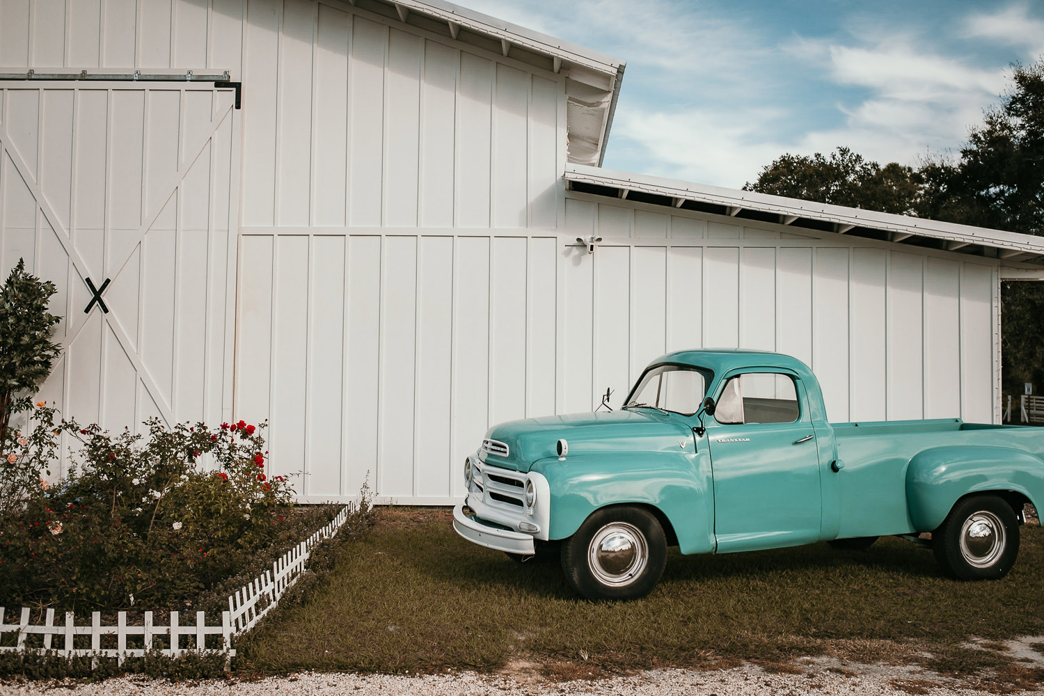 side of ever after barn with vintage blue pick up truck