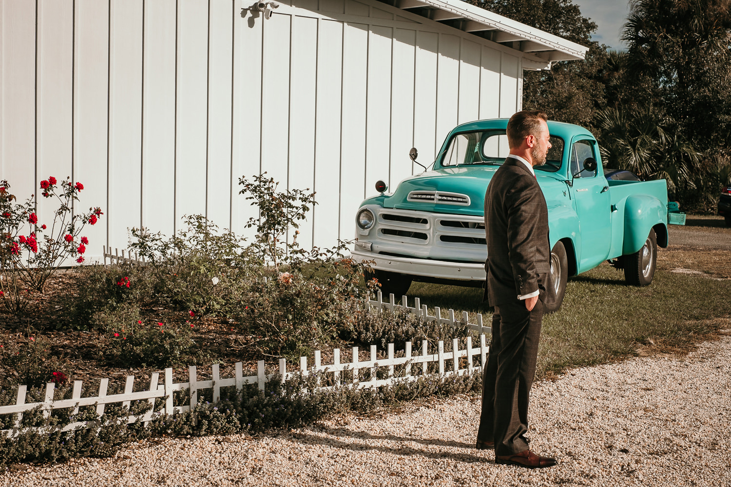 groom waiting outside near blue truck for first look