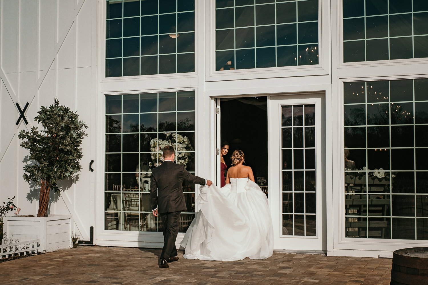 grooms holding brides dress as they enter the barn