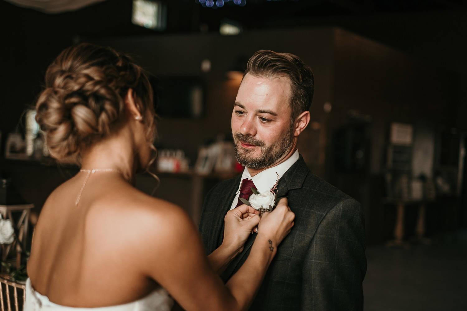 groom lovingly staring at bride putting on boutonnieres