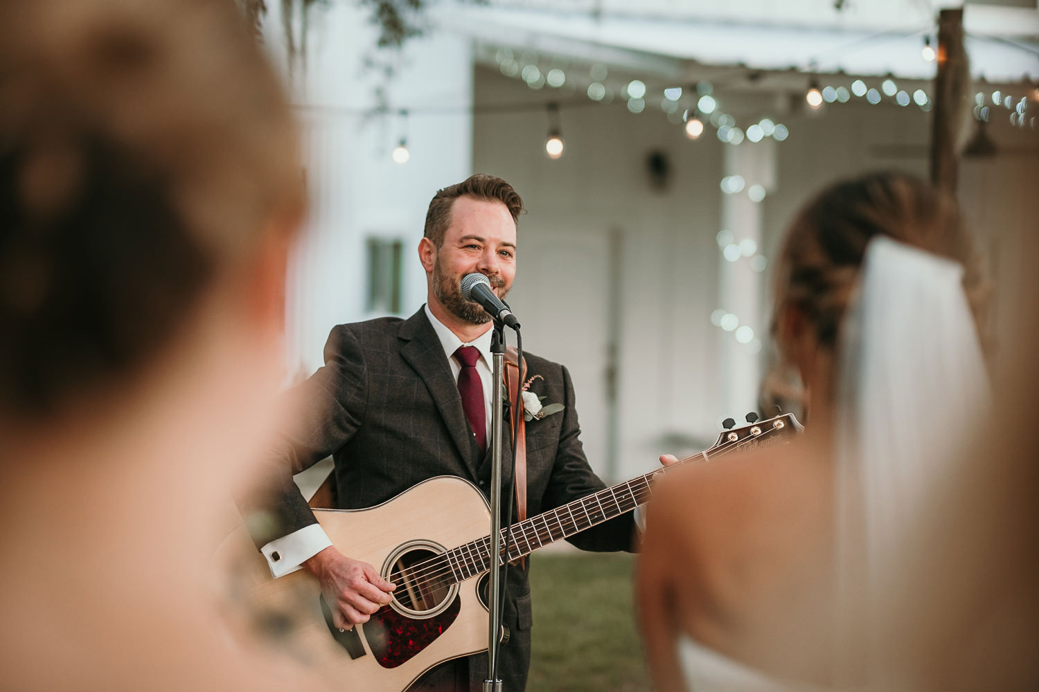 groom singing and playing guitar during ceremony