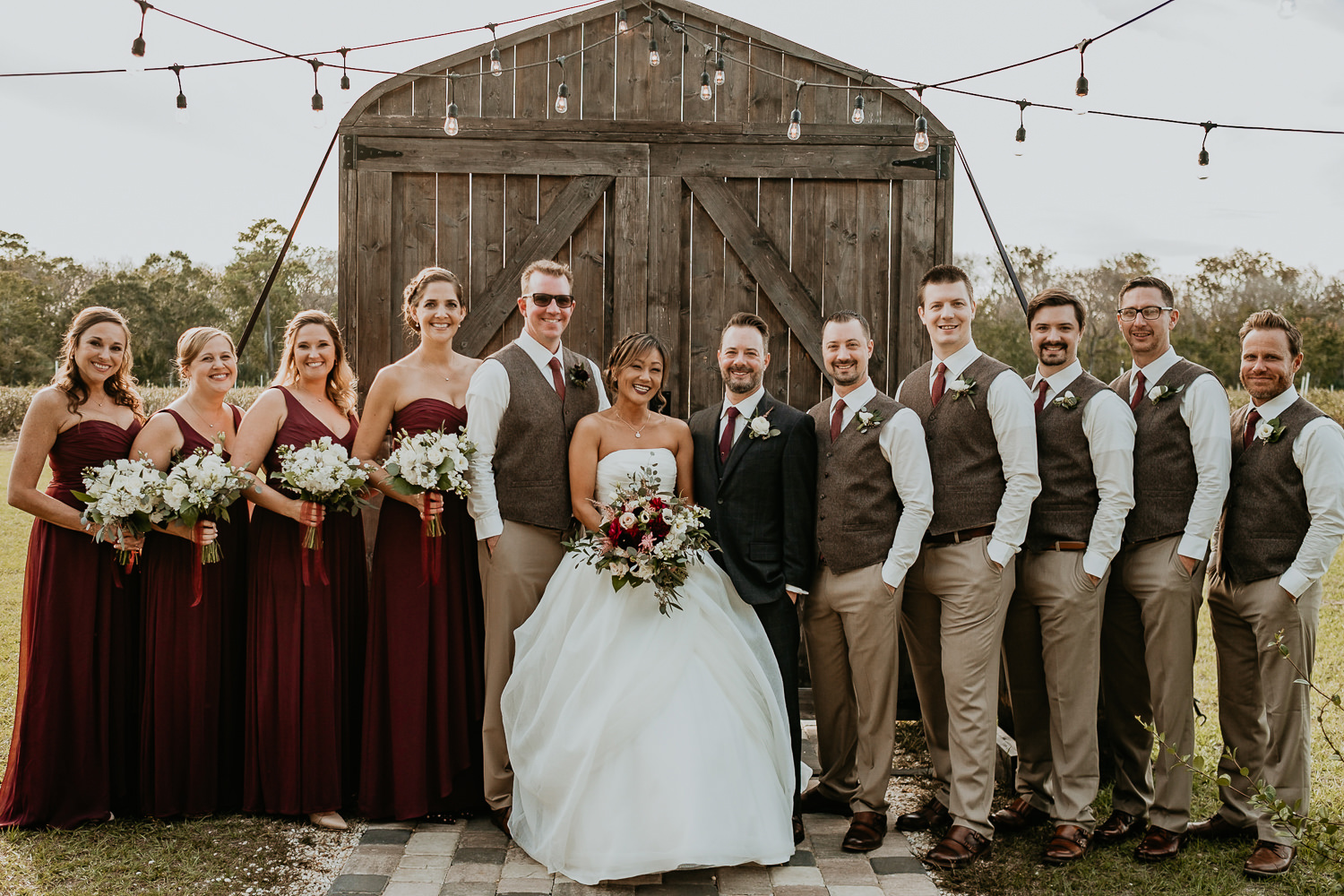 entire bridal party posing in front of wooden door