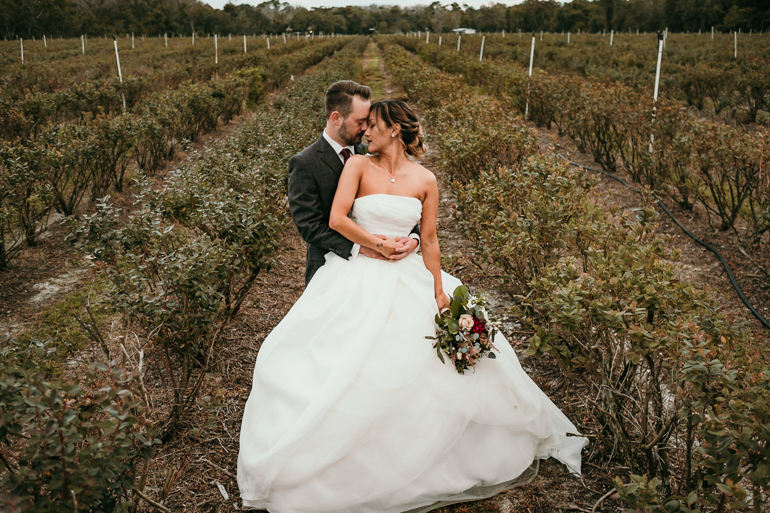 newlyweds posing in middle of green field foreheads touching