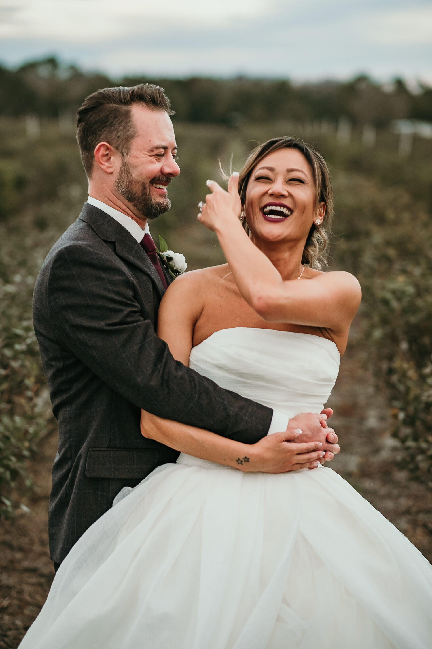 close up of newlyweds in middle of a field with bride laughing hard