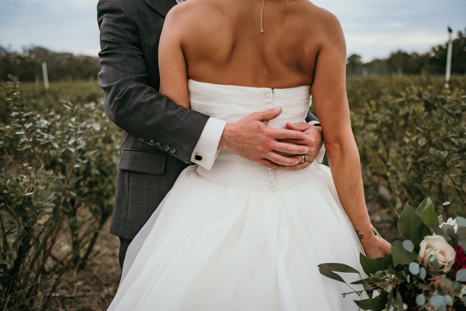 close up of wedding dress grooms arms around his bride