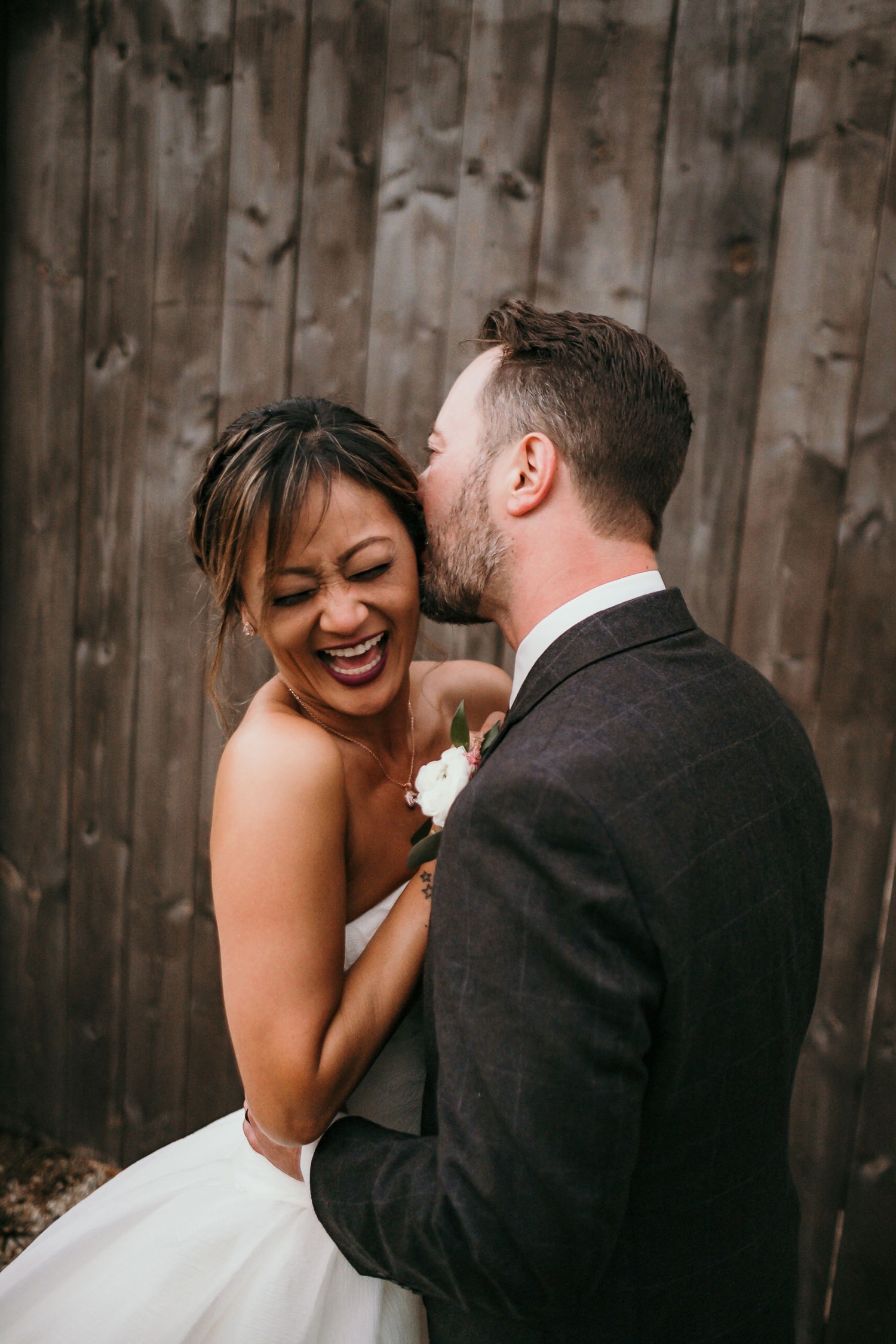 close up of groom kissing brides laughing face
