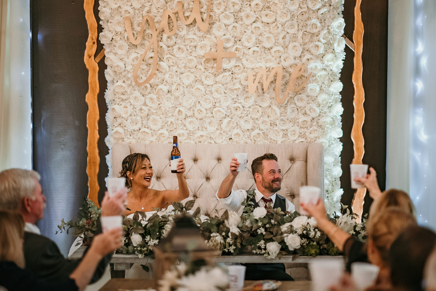newlyweds sitting and holding up beers cheering with crowd