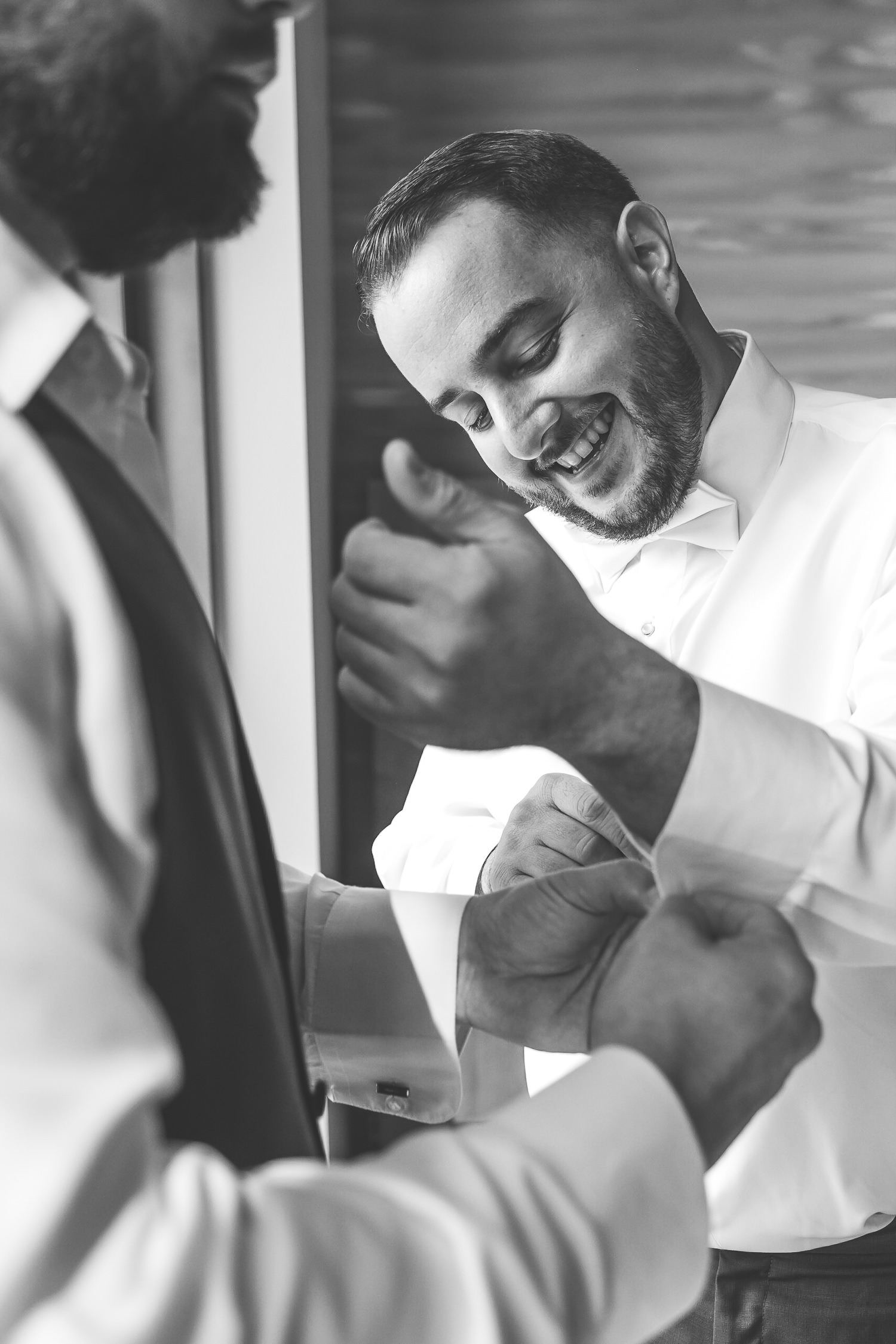 close up of groom fixing cuffing and smiling black and white