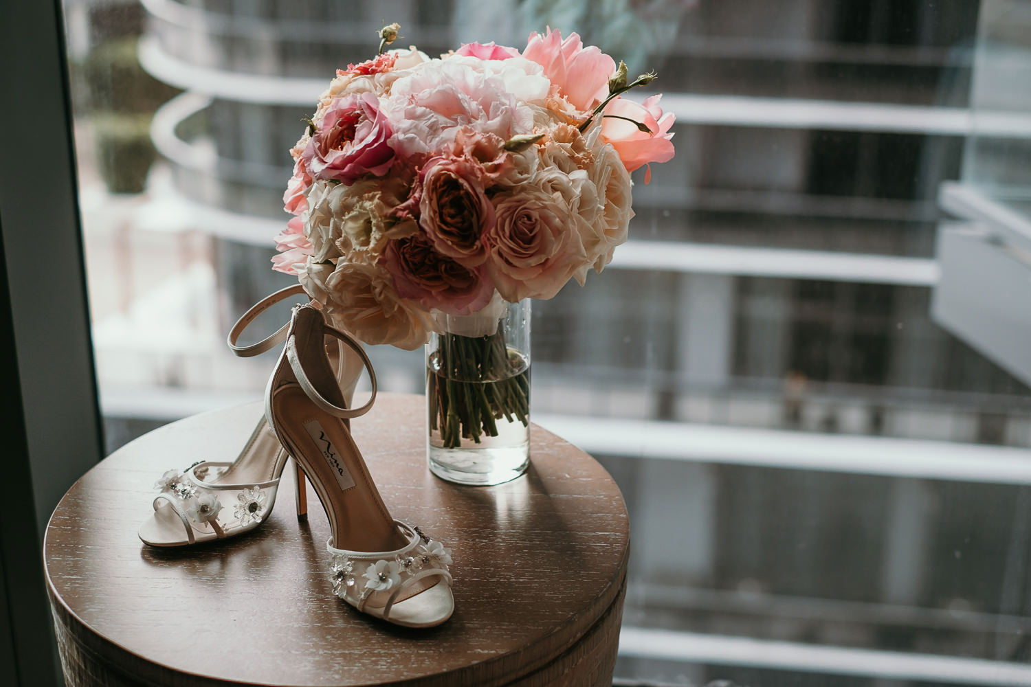 wedding shoes and flowers on small wooden table balcony view