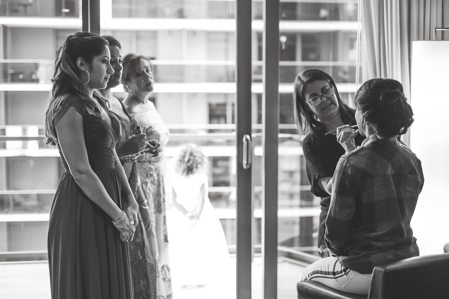 black and white bride sitting makeup artist applying brush family watching
