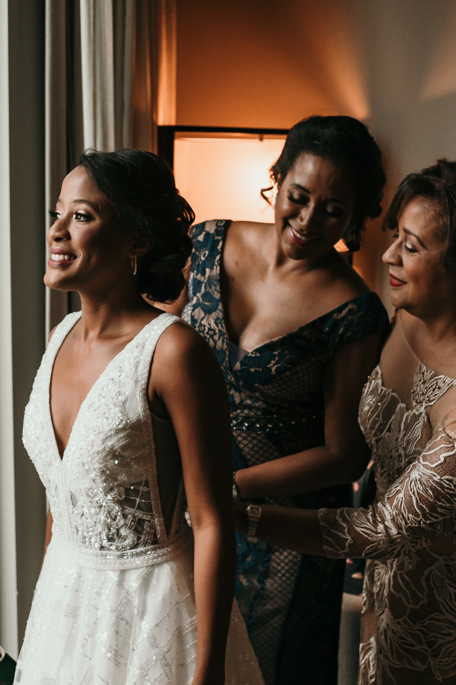 mother and sister helping bride get in dress