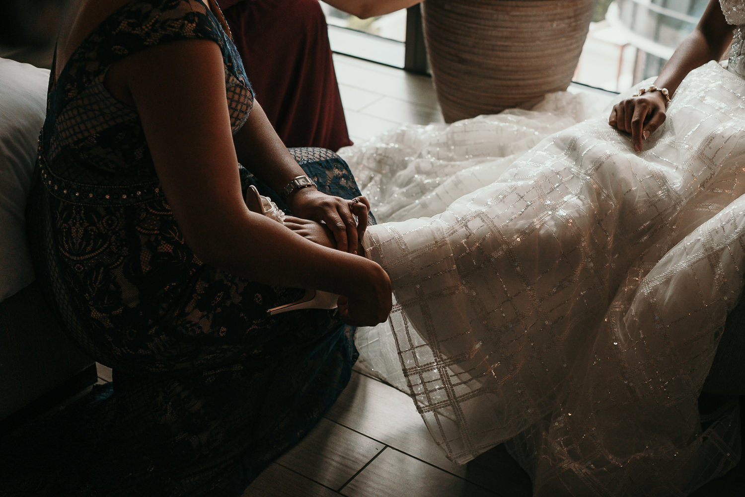 sister helping bride put on her shoes