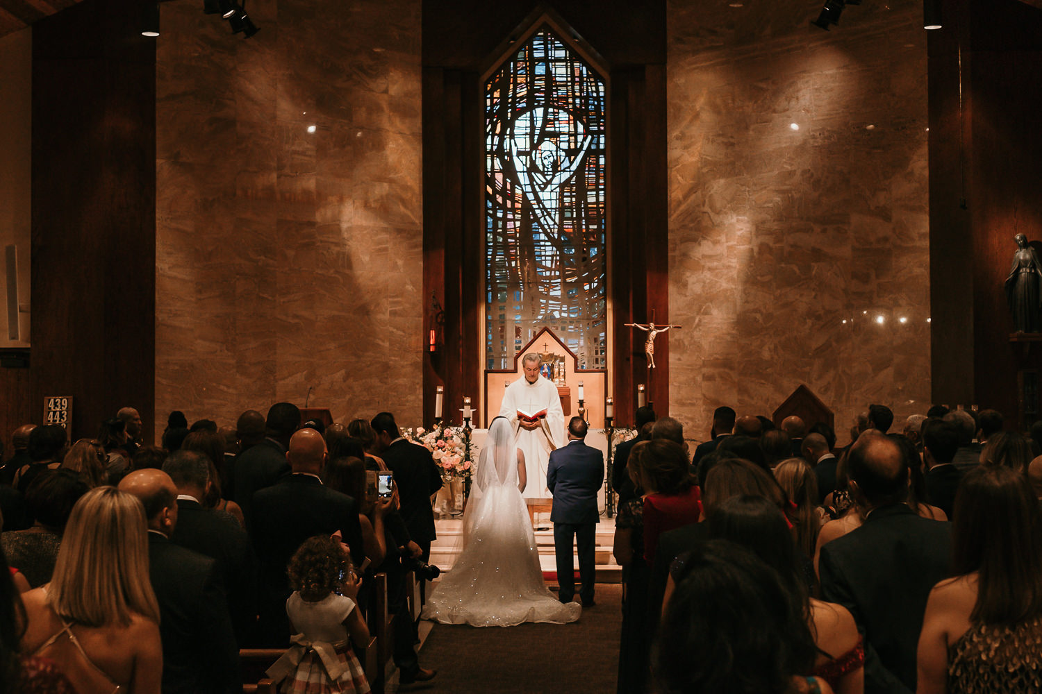 from back of church bride and groom standing facing altar