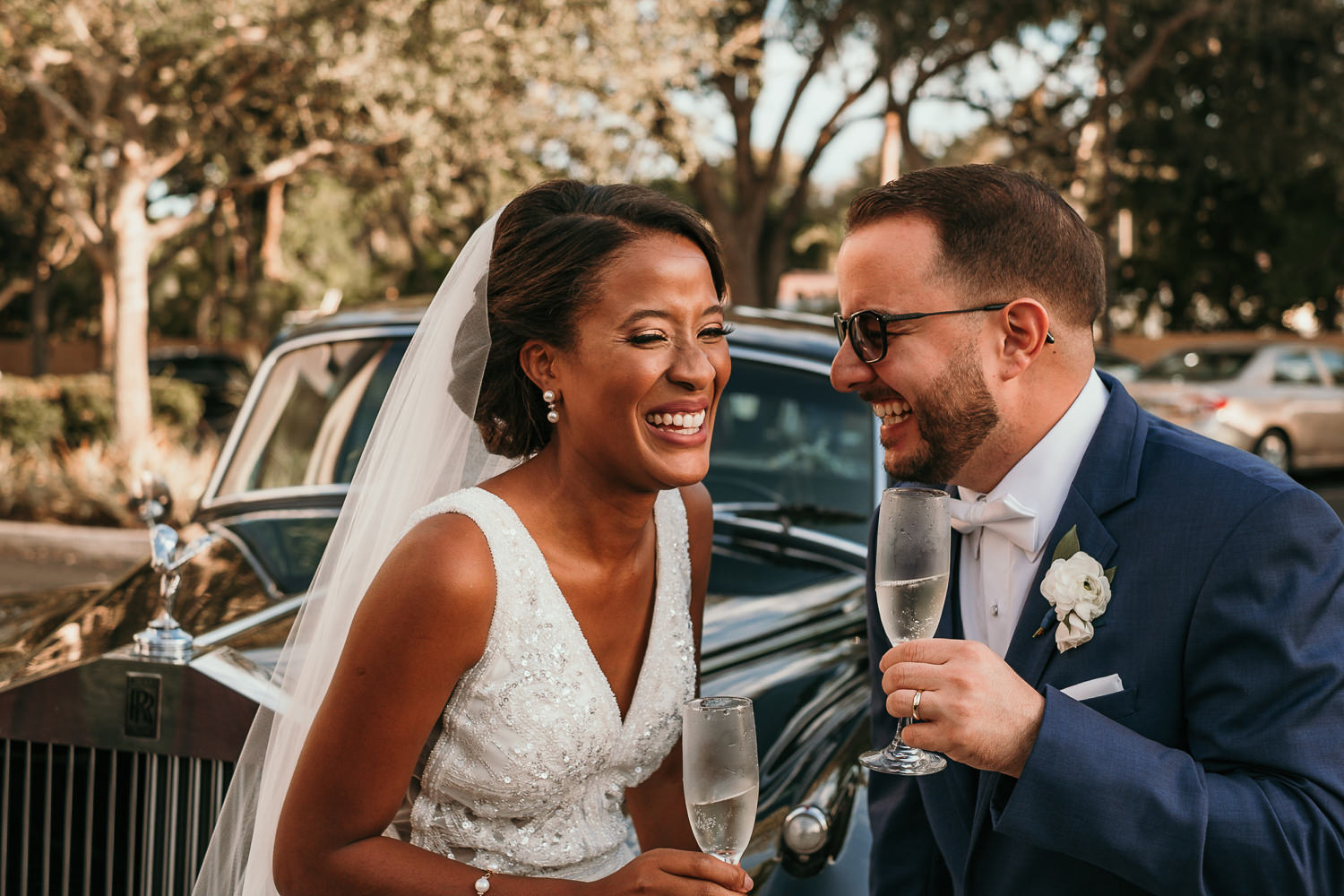 newlyweds laughing with each other holding champagne glasses