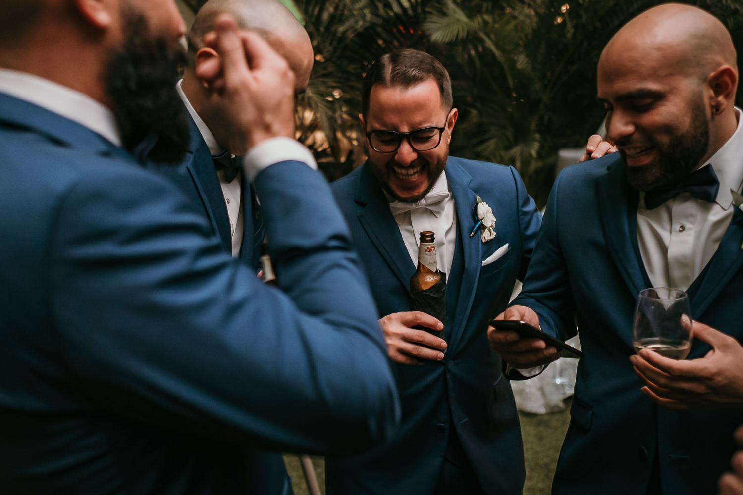 groomsmen huddled laughing groom with beer
