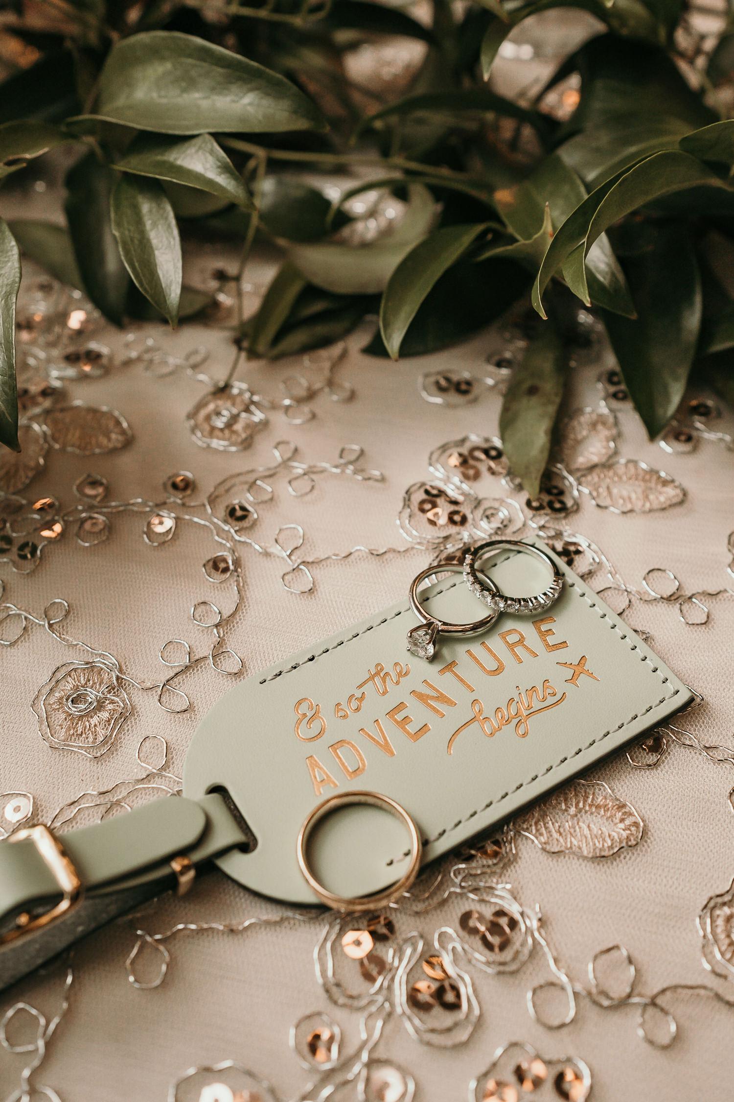 macro of wedding rings on suitcase tag