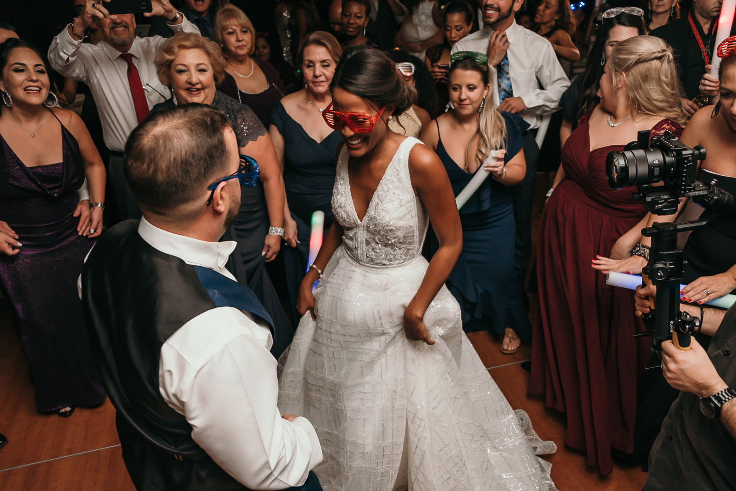 bride and groom dancing in middle of guests wearing big sunglasses