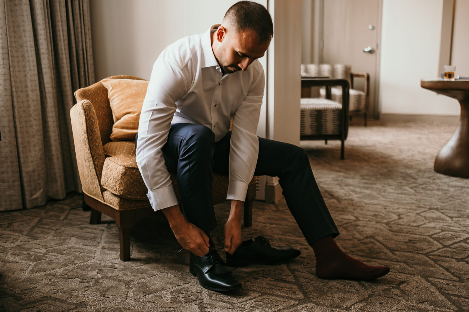 groom sitting putting on shoes on yellow loveseat