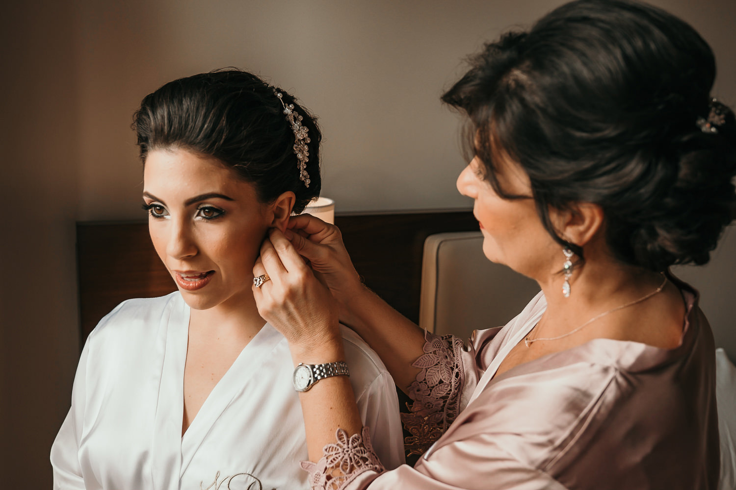 mother putting on bride's earrings