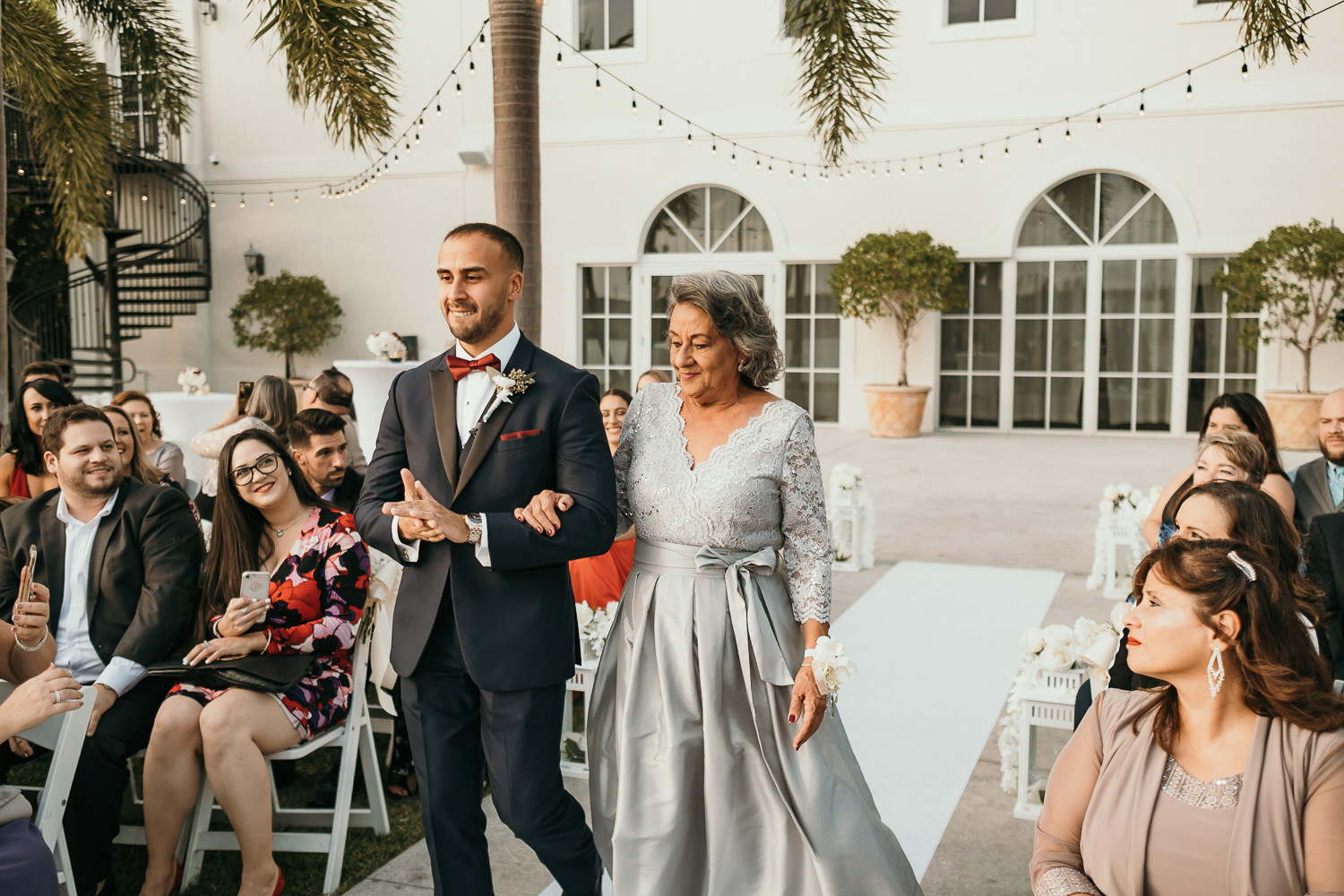 groom and his mother walking down aisle