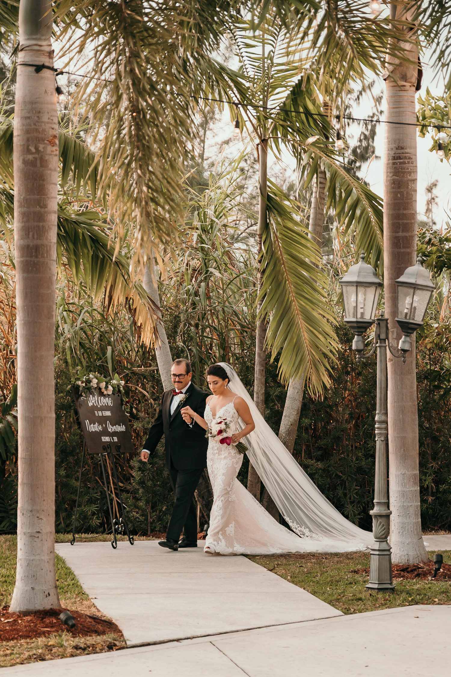bride and father walking towards ceremony area under palm trees