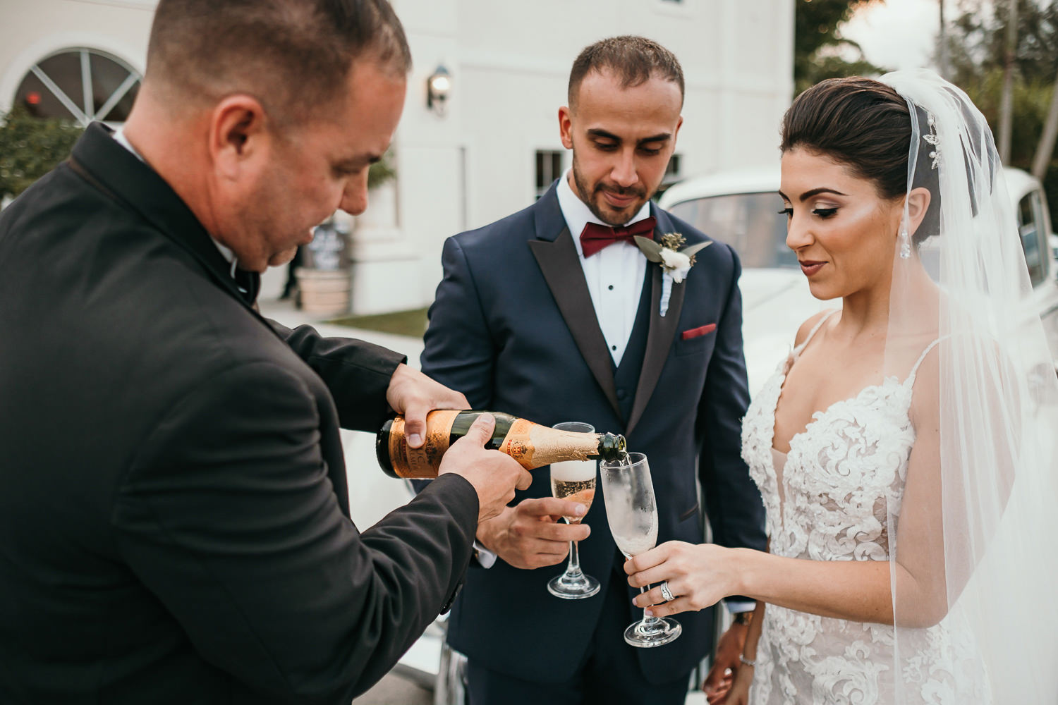 driver pouring newlyweds champagne