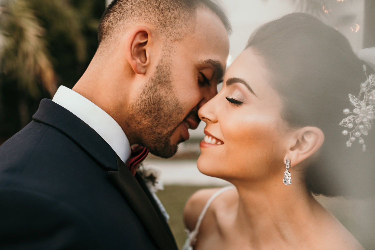 newlyweds almost kissing under veil