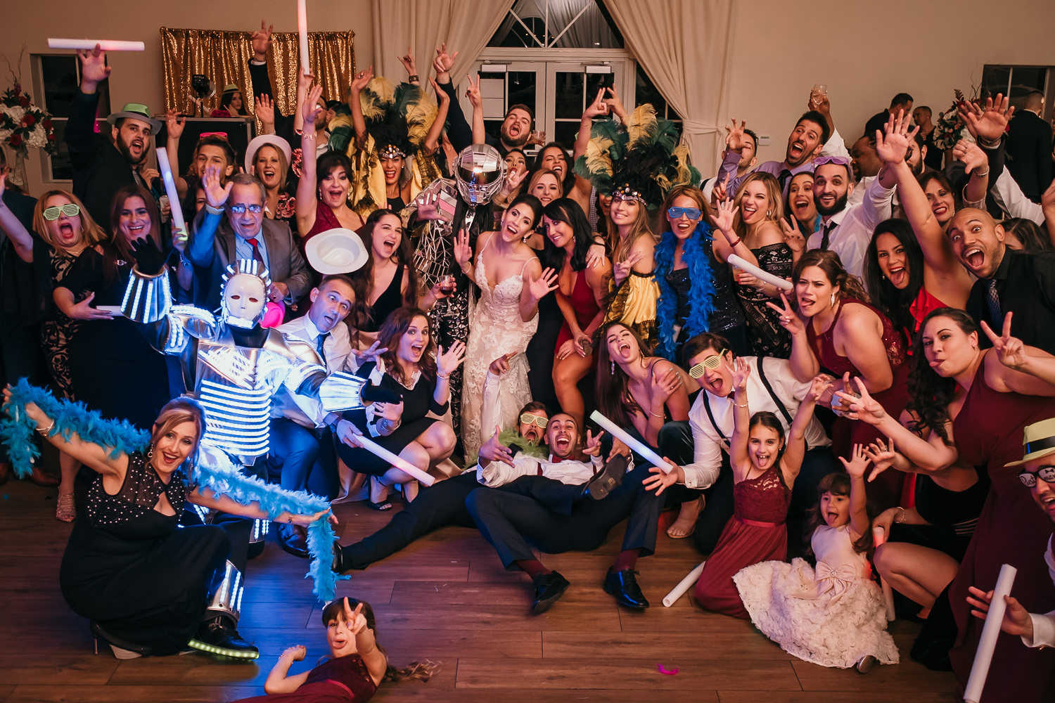 wide shot of entire wedding guests cheering at camera neon lights