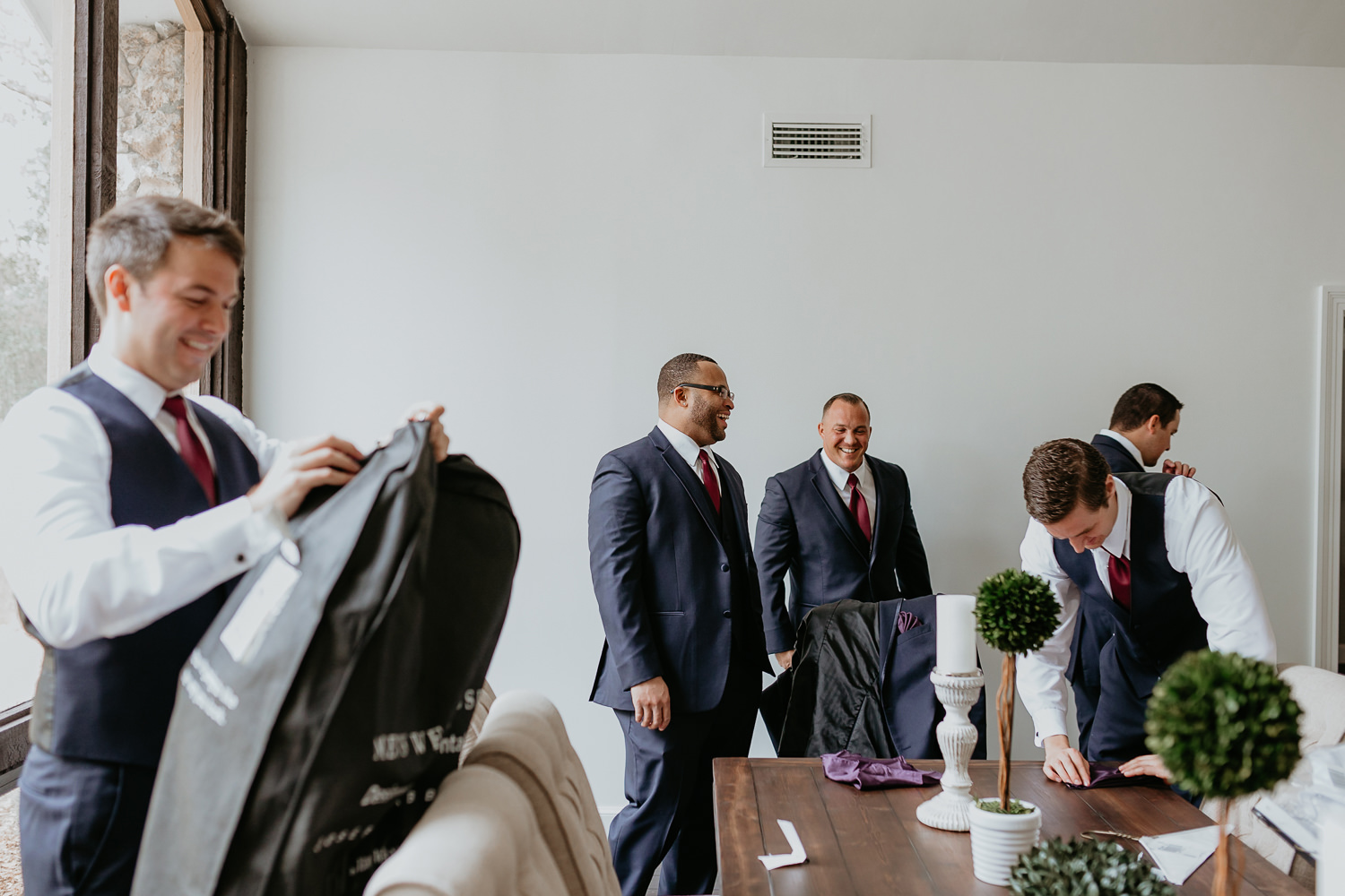 groomsmen laughing one man on left opening his suit carrier