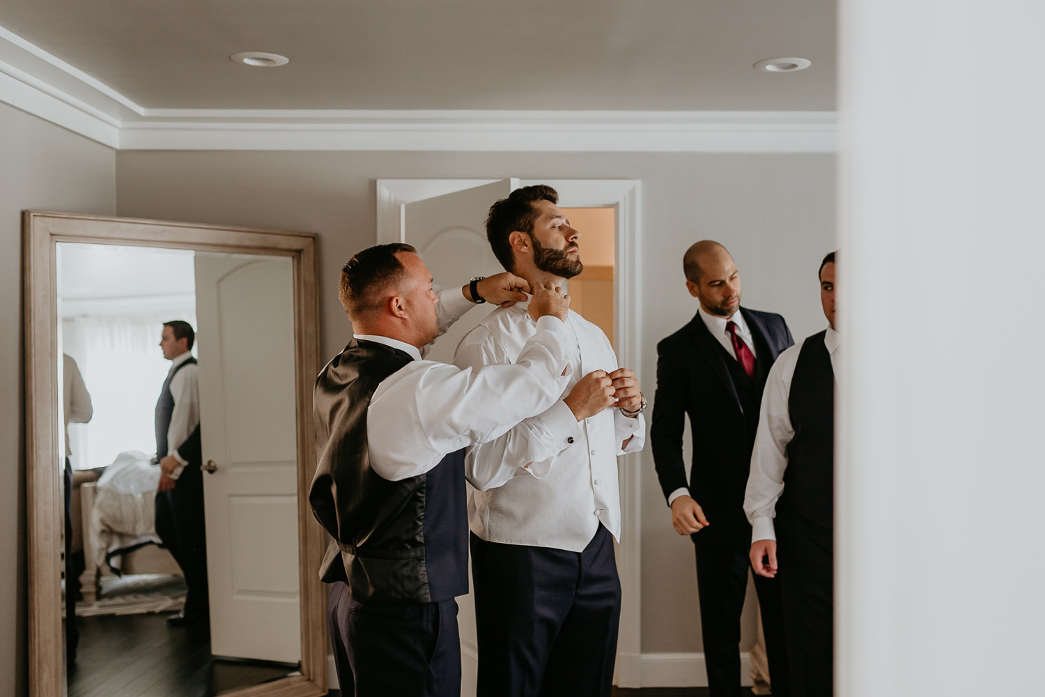 best man helping groom with his tie from behind