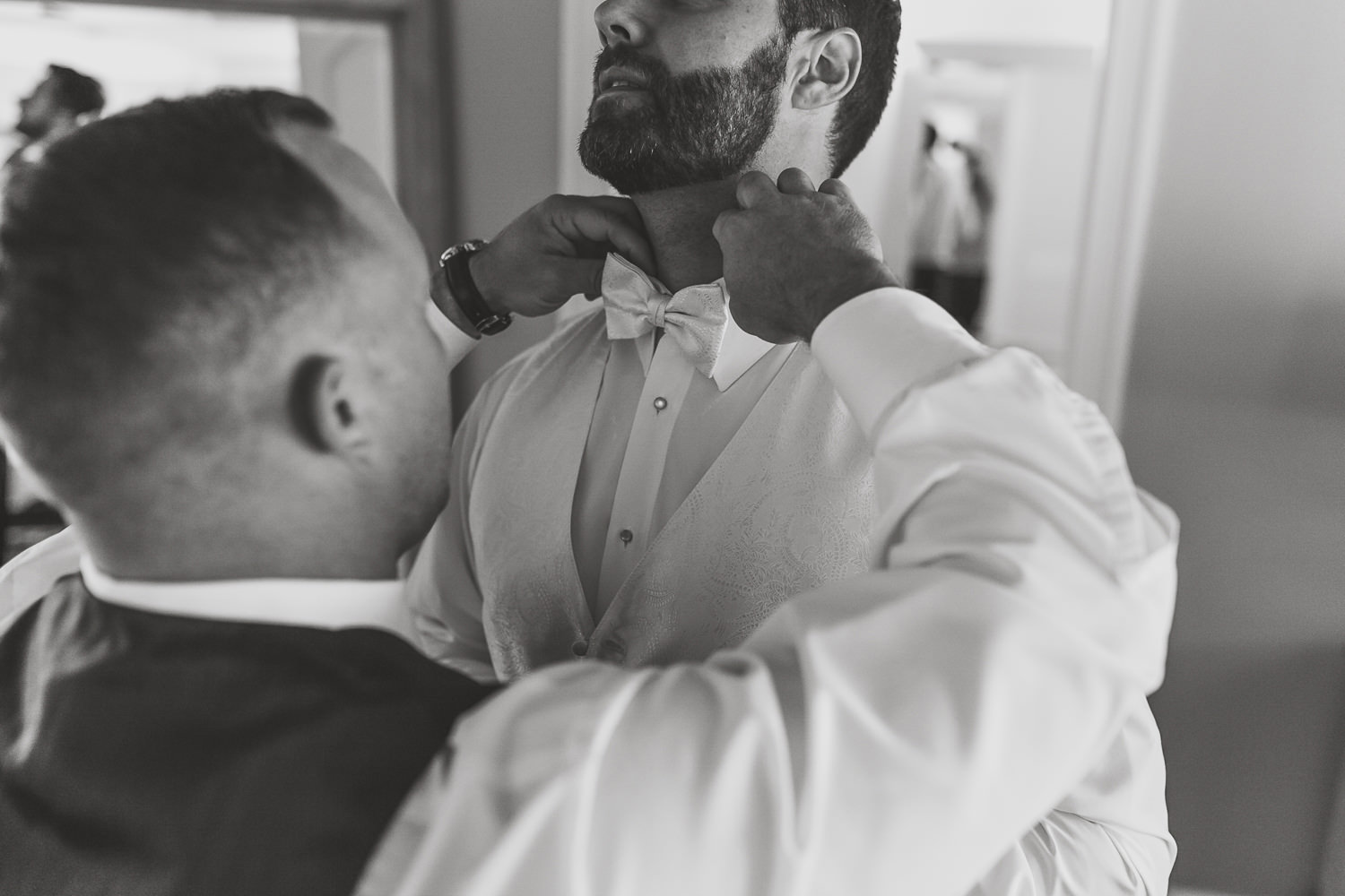 closeup of best man helping groom with bow tie from the front