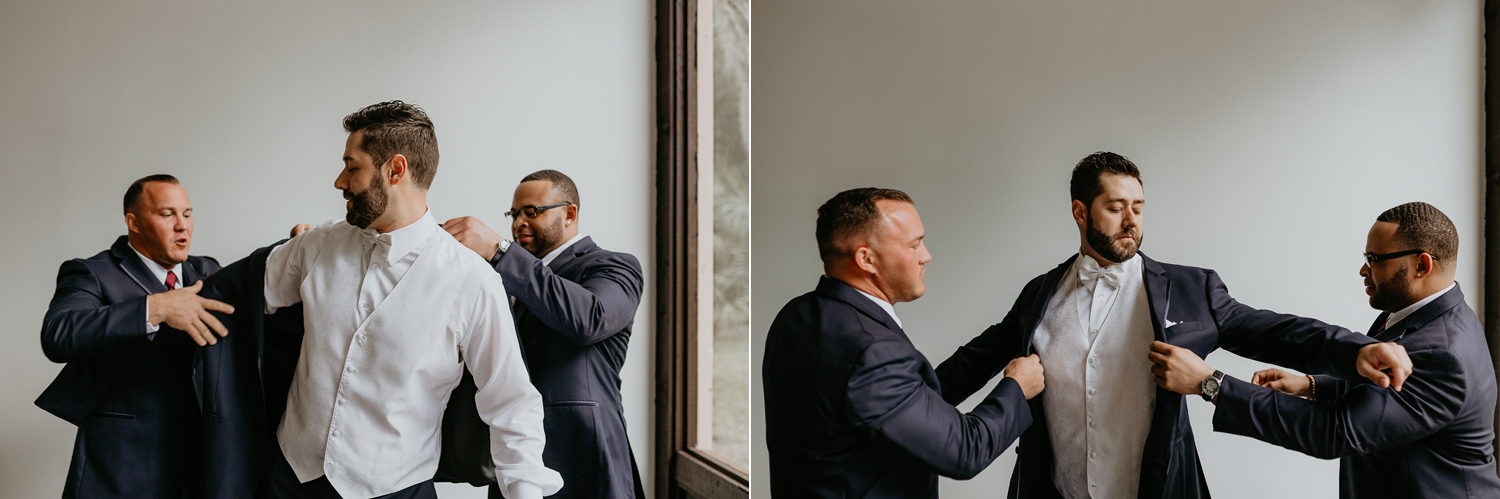 two groomsmen helping the groom put his blazer on