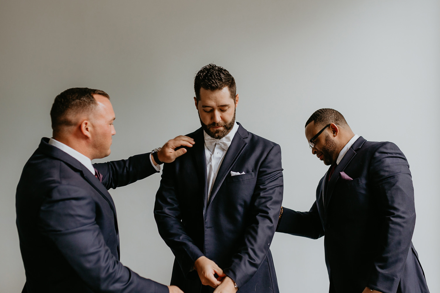 two groomsmen dusting off the groom's suit making sure he looks fly