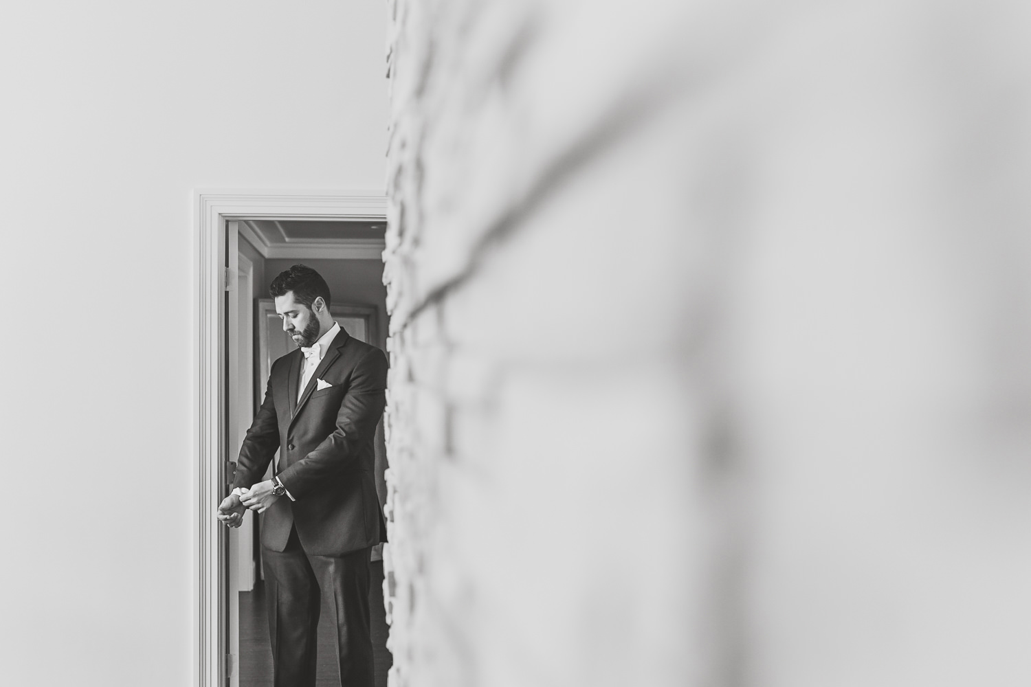 black and white of groom fixing his sleeve next to brick wall
