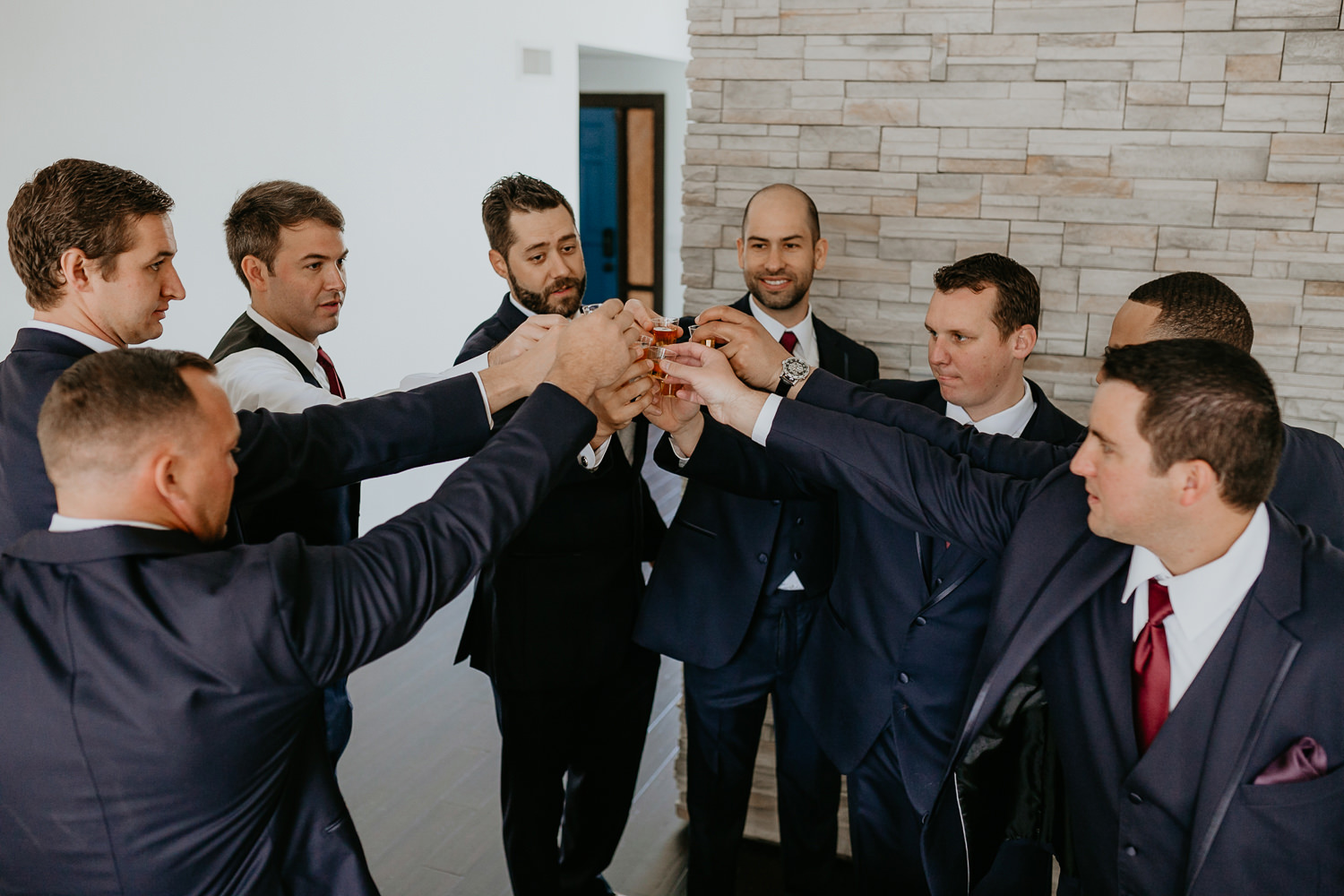 groom and groomsmen cheering their drinks