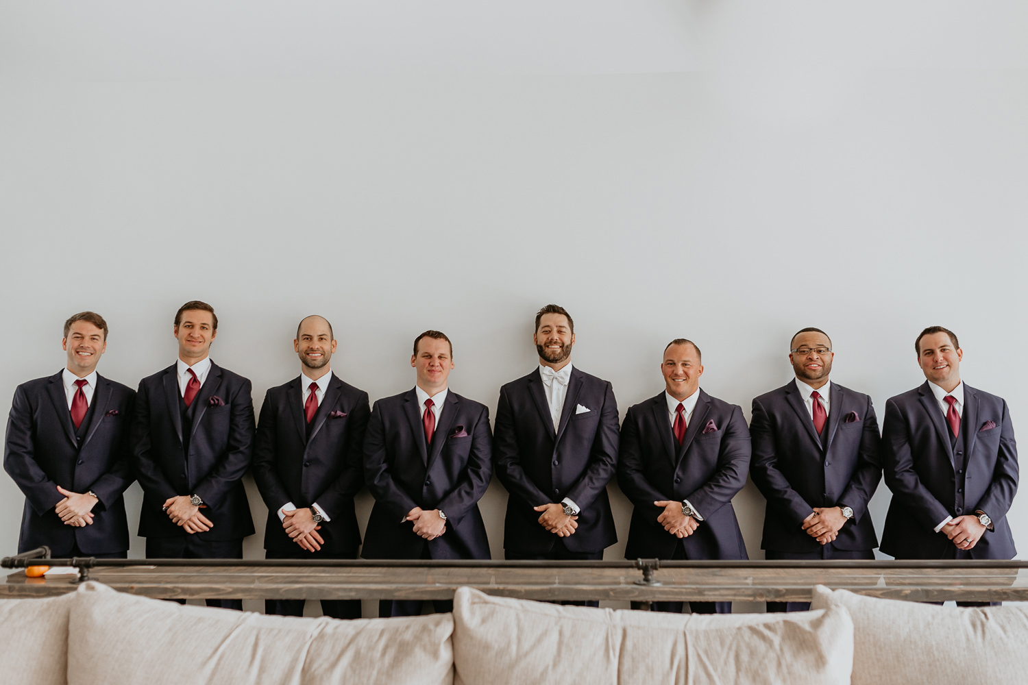 groom and seven groomsmen lined up smiling at camera in front of white wall