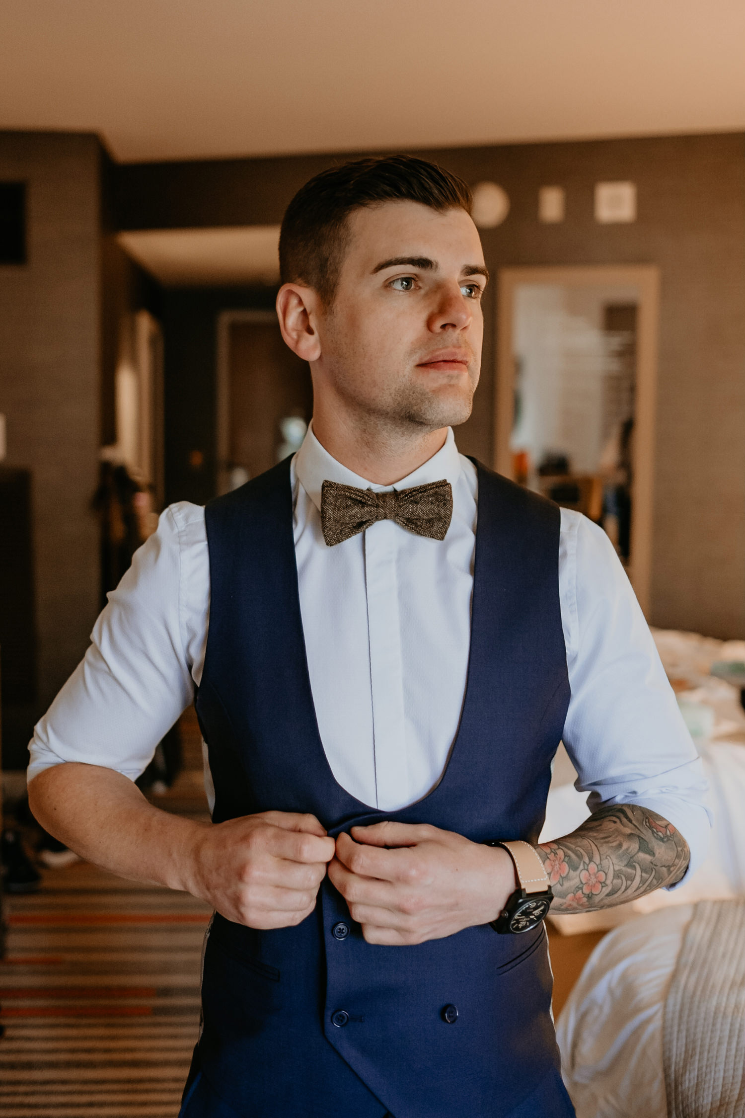 groom to be fixing his vest inside hard rock hotel room