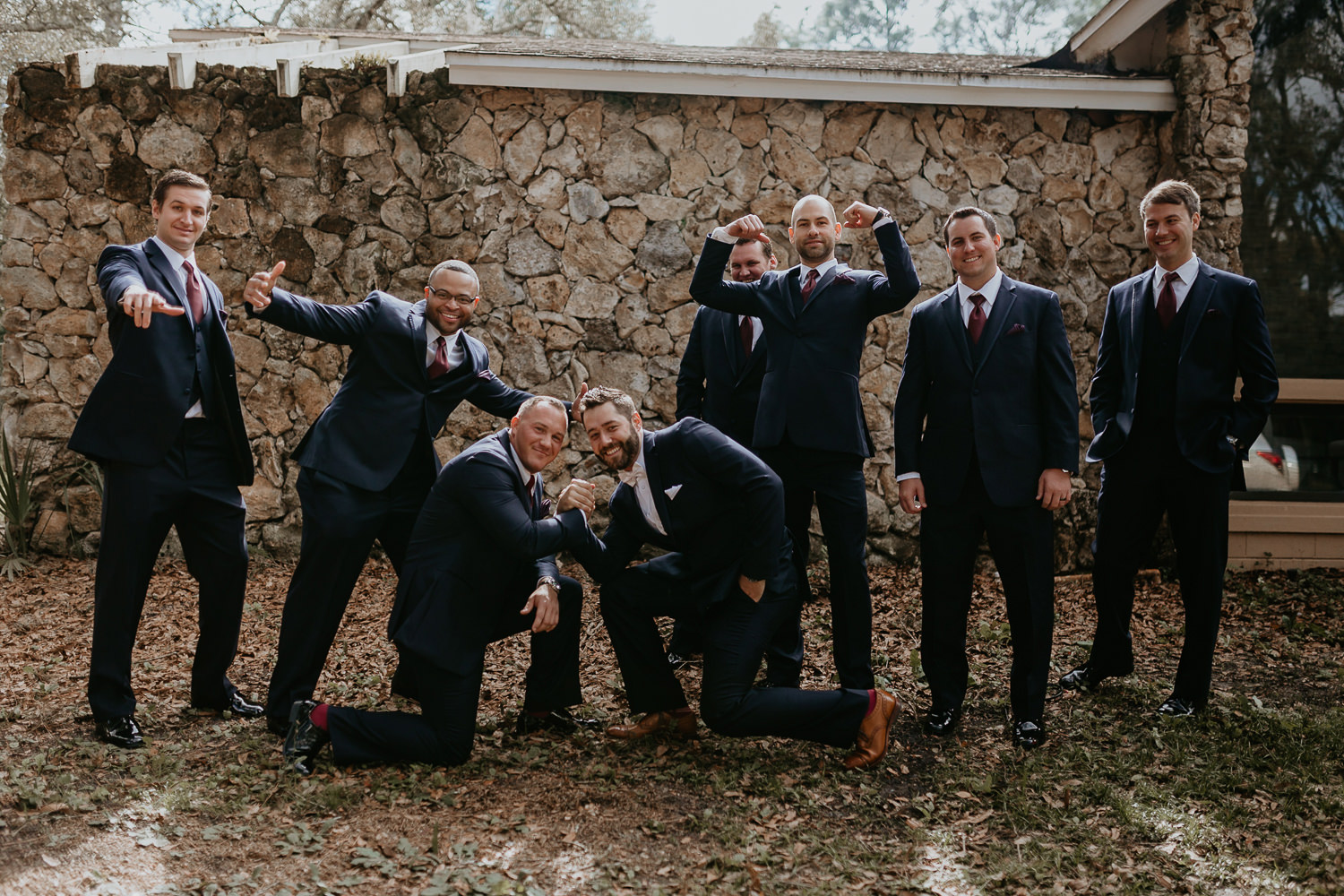 groomsmen flexing in front of stone wall outside of the house