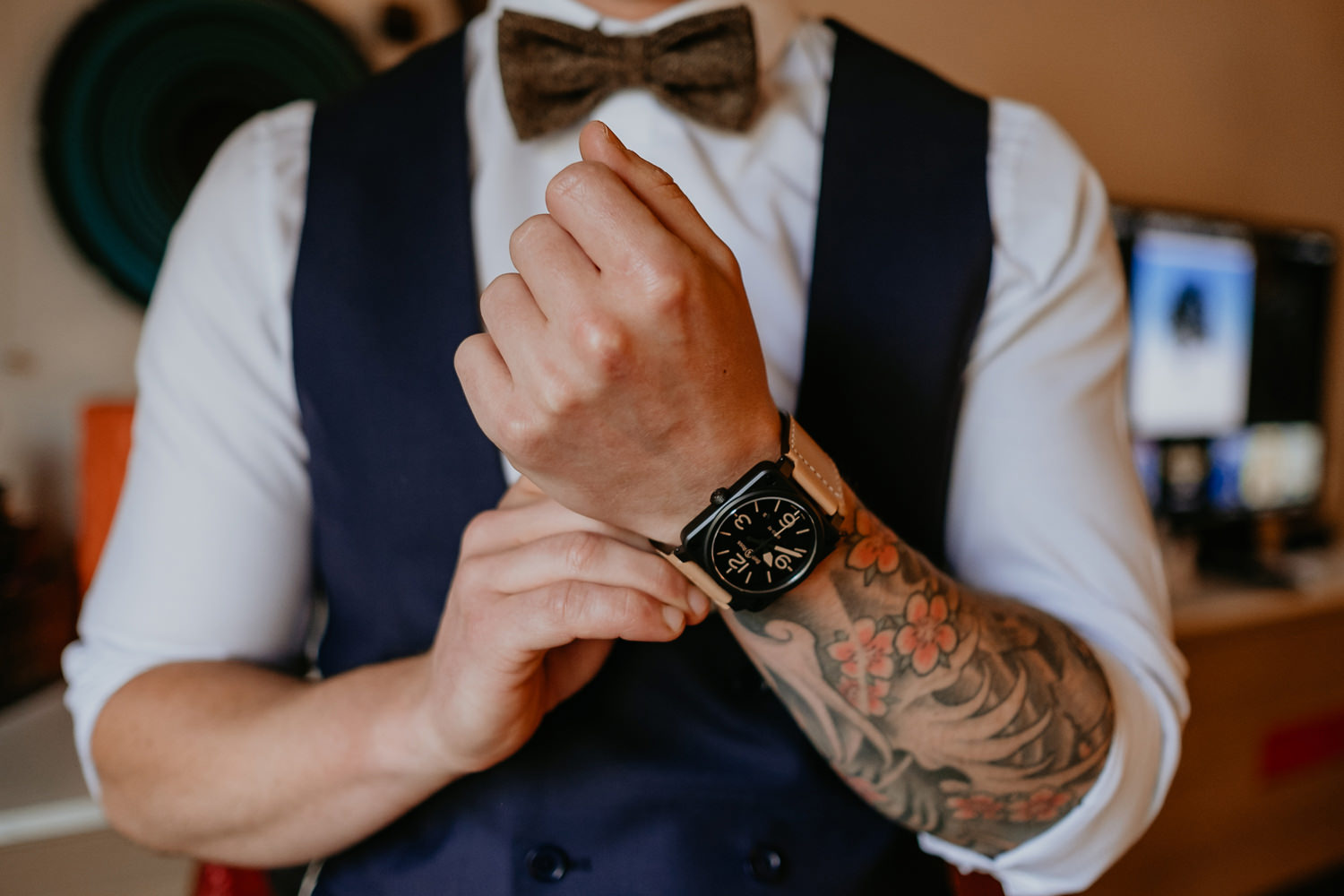 close up of groom fixing his watch